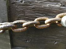 Old rusty chain on wood royalty free stock photo