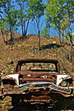 Old rusty clasic car looking angry bent bumper in bush . Old rusty classic car looking angry bent bumper in bush with rock and trees Royalty Free Stock Images