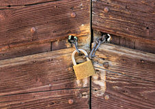 Old rusty closed door. Metallic Padlock on a chain closing a wooden door Stock Photography