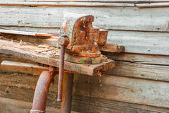 Old rusty clumping device on weathered work bench Royalty Free Stock Image