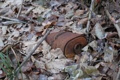 Old rusty coal filter of gas mask RKKA is thrown in the forest among the fallen leaves Royalty Free Stock Photography