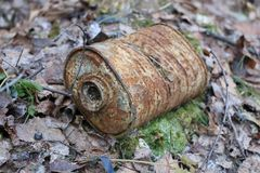 Old rusty coal filter of gas mask RKKA is thrown in the forest among the fallen leaves Stock Images