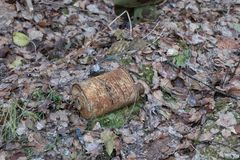 Old rusty coal filter of gas mask RKKA is thrown in the forest among the fallen leaves Royalty Free Stock Images