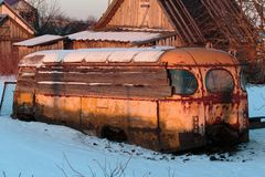 Old rusty and collapsed bus shrouded in snow. Stock Image