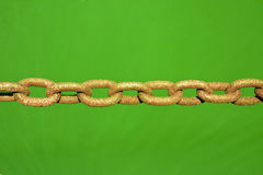 Old rusty colored chain on green background - toned image Stock Image