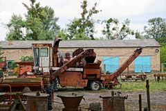 Old rusty combine and scrap metal in a field near a brick building Stock Photos