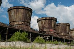 Old rusty cooling towers against a blue sky royalty free stock photography