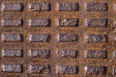 Old rusty corrugated metal manhole cover, cast iron with rectangles royalty free stock image