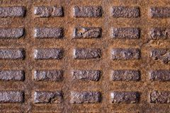 Old rusty corrugated metal manhole cover, cast iron with rectangles royalty free stock photo