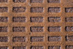 Old rusty corrugated metal manhole cover, cast iron with rectangles stock photography