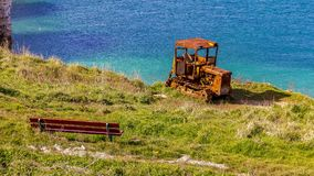 Flamborough North Landing, East Riding of Yorkshire, UK. Old rusty crawler and and a bench, Flamborough North Landing near Bridlington, East Riding of Yorkshire royalty free stock image