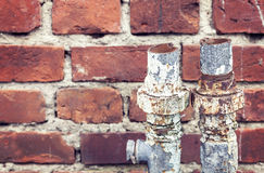 Old rusty cut pipes on a brick wall background Stock Images