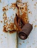 An old rusty cylinder padlock on a rusty metal gate Royalty Free Stock Image