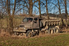 Old rusty Czech military truck. Abandoned rusty car. Lorry and overgrown grass. Stock Photos