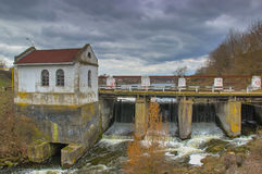 Old rusty dam on a river at cloudy sky Stock Images