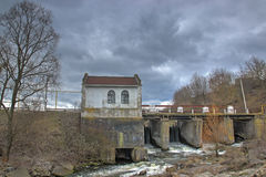 Old rusty dam on a river at cloudy sky Stock Image