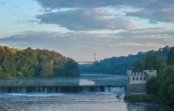 Old rusty dam on a river at cloudy sky. Old rusty dam in the river at dark sky Royalty Free Stock Photos