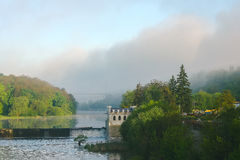 Old rusty dam on a river at cloudy sky. Old rusty dam in the river at dark sky Stock Photo