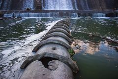 Old rusty dam on a river at cloudy sky Stock Photo