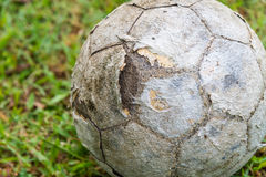 Old rusty and damage football on green grass Stock Photography