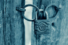 Old Rusty Decorated Padlock on a Wooden Door in Cyan. Royalty Free Stock Photo