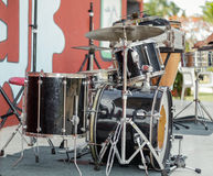 Old rusty dirty drum kit on outdoor concert stage. Black vintage jazz style drum set standing on the stage and awaiting for its drummer to give a great royalty free stock photo