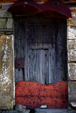 Old rusty door. Detail of an old rusty door on a stone house Royalty Free Stock Photo