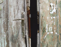 Old rusty door. Grunge wooden door and handle. Horizontal color photo Royalty Free Stock Photo