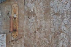 Old rusty door handle on a wooden door with peeling paint royalty free stock images