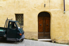An old and rusty door. An old house and its rustic door with a classic italian car Stock Photography
