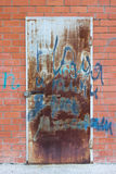 Old rusty door. In masonry with graffiti Stock Image