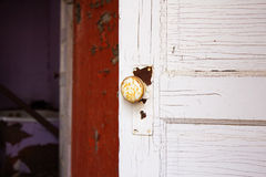 A white rusty doorknob on a white door Royalty Free Stock Photography