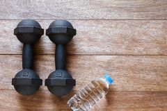 Old rusty dumbbells with drinking water bottle on vintage wooden floor royalty free stock photo