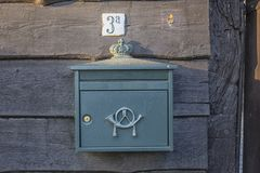 An old, rusty dutch mailbox hangs on the wall of an abandoned wooden house royalty free stock photography