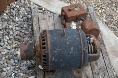 An old, rusty engine lies on a board. Royalty Free Stock Image