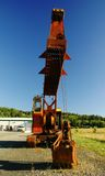 Old rusty excavator boom at low angle. Old excavator with empty cabin, front view in perspective Stock Photos