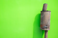 Old rusty exhaust pipe on green wall. Royalty Free Stock Photography