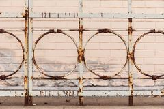 Old rusty fence on the background of a brick house. royalty free illustration