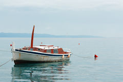 Old rusty fishing boat stands empty on the water, blue sky Stock Photo