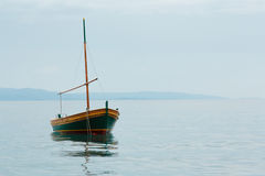 Old rusty fishing boat stands empty on the water, blue sky Stock Photos
