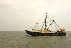 Old, rusty fishing trawler in early morning mist Stock Image