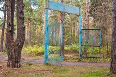 Old rusty gate to the children`s pioneer camp in the autumn forest royalty free stock photography