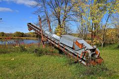 Old rusty grain elevator. An old grain elevator with a folded back hopper is left in the long grass and autumn colored leaves Royalty Free Stock Photos