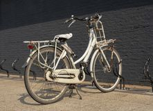 Old rusty grunge vintage white bike in bicycle rack in front of a black brick wall. stock photos