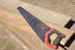 An old rusty hacksaw on the board. Building tools Stock Images