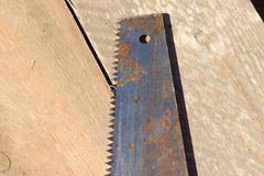 An old rusty hacksaw on the board. Building tools Stock Photo
