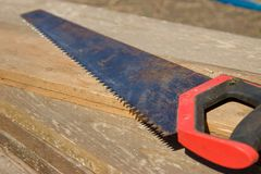 An old rusty hacksaw on the board. Building tools Royalty Free Stock Images