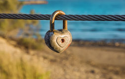 Old rusty heart shaped padlock on bridge metal cable. Old rusty heart shaped padlock with peeled off red paint in enlarged view as symbol of eternal love Stock Photos