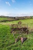 Old rusty horse drawn hay rake in a grass field with Devonshire countryside and hills in the background royalty free stock photos