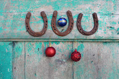 Old rusty horseshoe and Christmas baubles on wooden door Stock Image